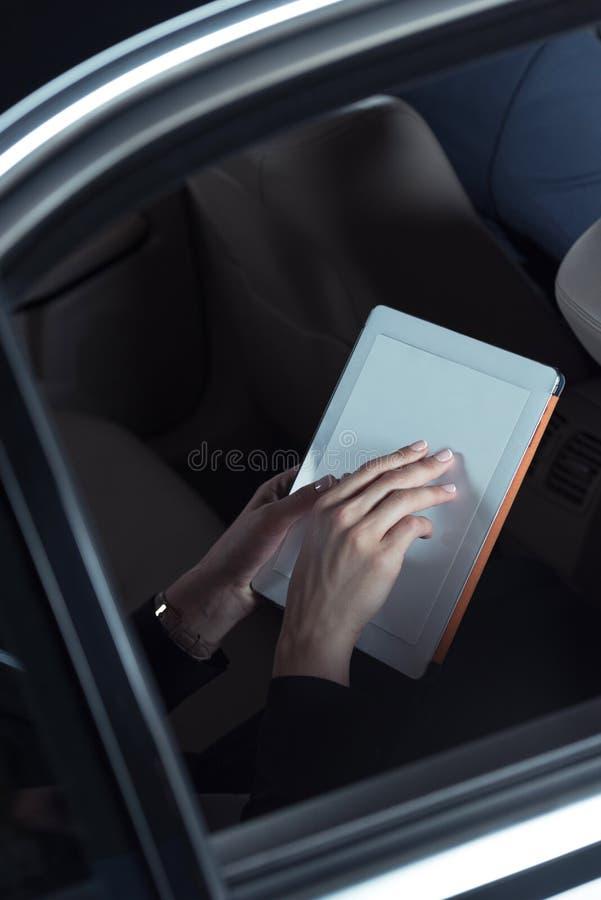 vrouw die digitale tablet in auto gebruiken royalty-vrije stock foto's