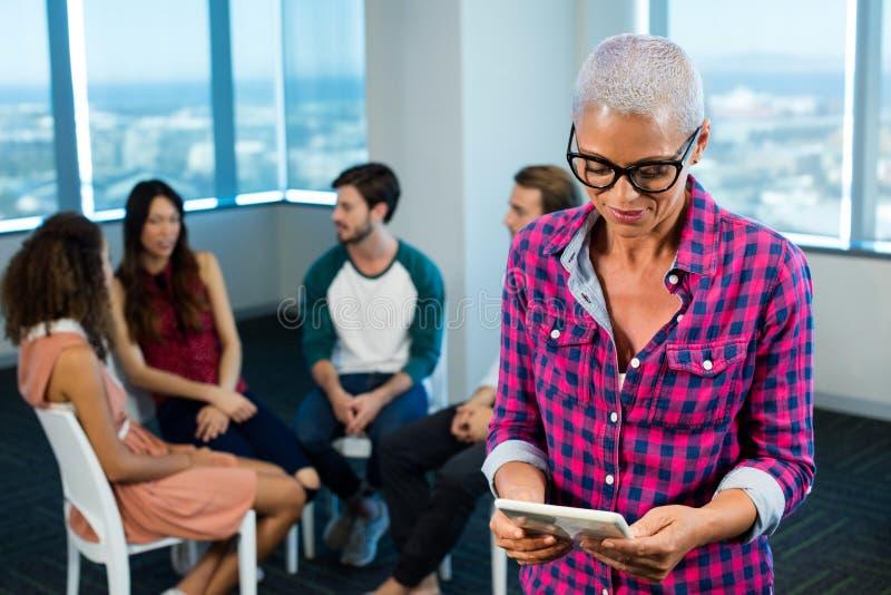Vrouw die digitale tablet gebruiken terwijl creatief commercieel team op achtergrond royalty-vrije stock fotografie