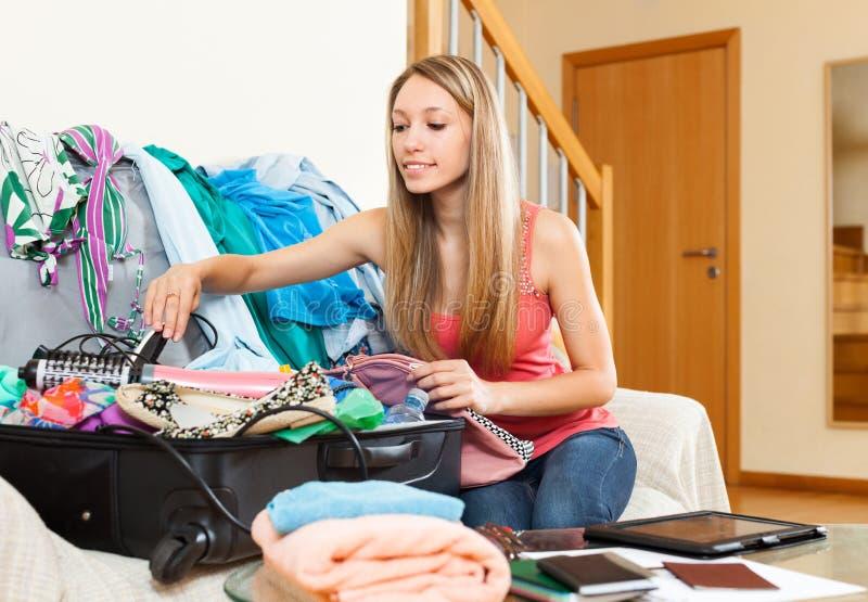 Vrouw die dingen in een open koffer zetten royalty-vrije stock afbeeldingen