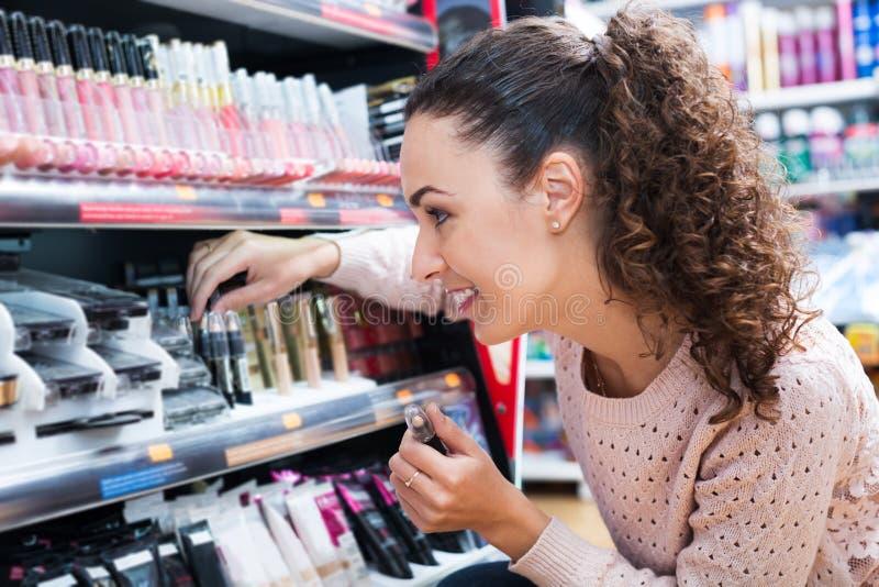 Vrouw die dingen voor make-up kiezen stock afbeeldingen