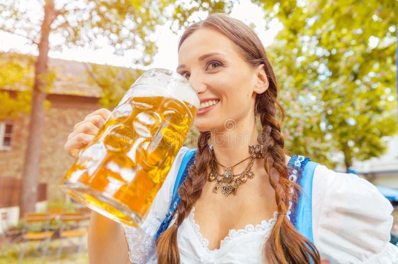 Vrouw die Dirndl-het drinken bier dragen stock foto's