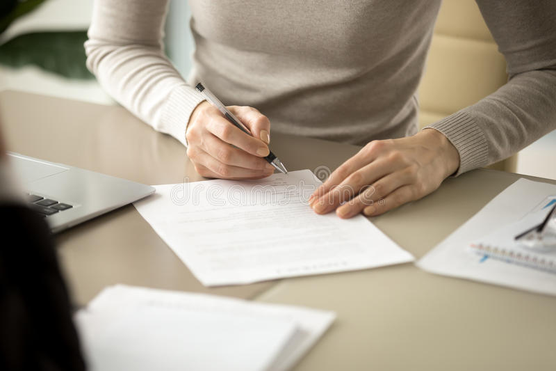 Vrouw die document, nadruk op vrouwelijke hand ondertekenen die handtekening zetten, stock afbeeldingen