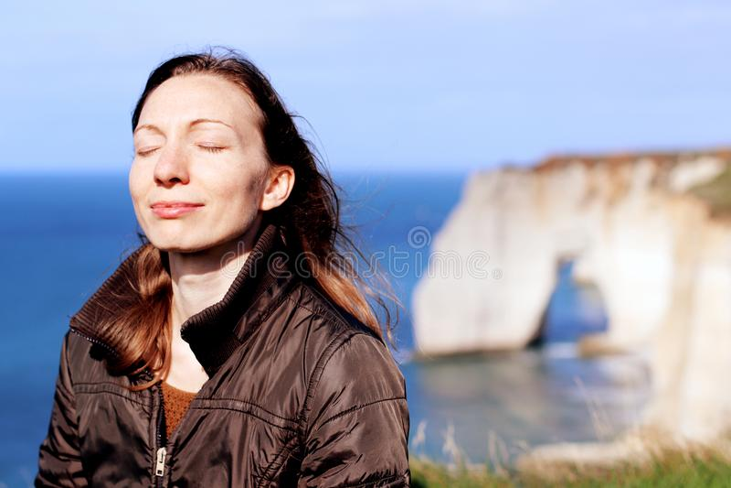 Vrouw die doend ademoefeningen bovenop de klippen van Normandië in de lente glimlachen stock fotografie