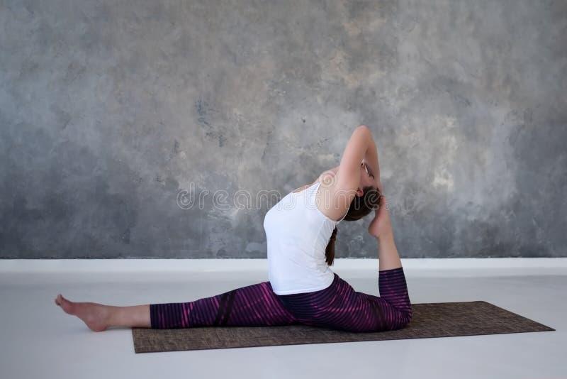 Vrouw die, doend yoga of pilates oefening uitwerken Aapgod, hanumanasana stock afbeeldingen