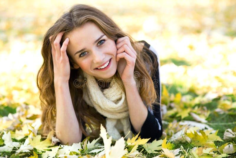 Vrouw die door de herfstbladeren wordt omringd stock afbeelding