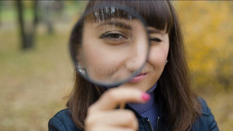 Vrouw die door meer magnifier kijken stock video