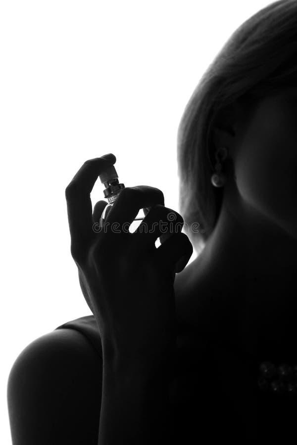 Vrouw die door parfum haar hals spuiten stock foto's