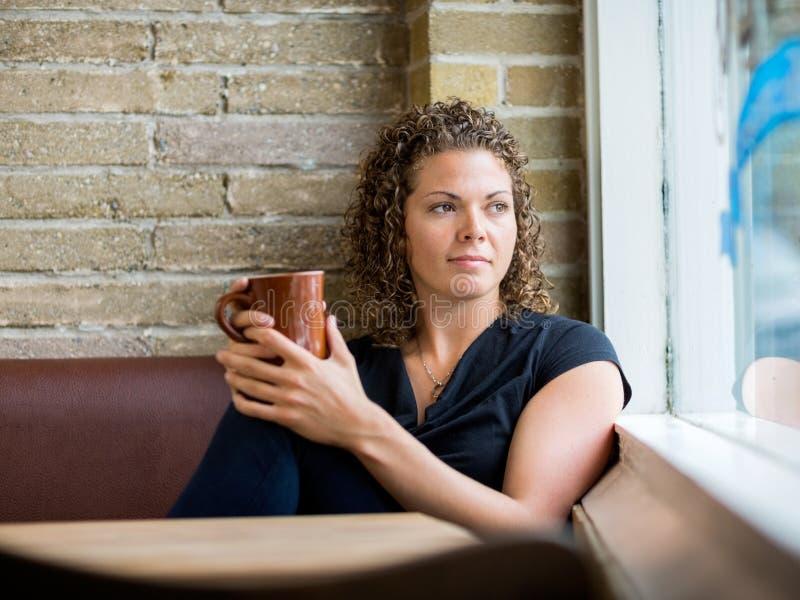 Vrouw die door Venster Cafetaria bekijken stock afbeeldingen