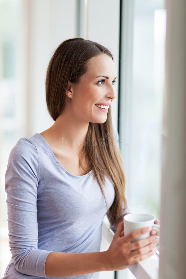 Vrouw die door venster kijken stock afbeelding