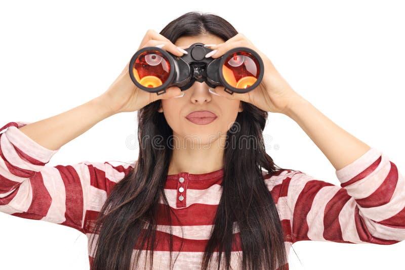 Vrouw die door zwarte verrekijkers kijken royalty-vrije stock fotografie