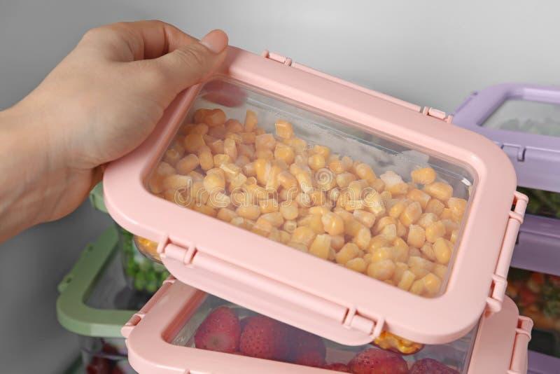 Vrouw die doos met graanpitten nemen van ijskast, royalty-vrije stock fotografie