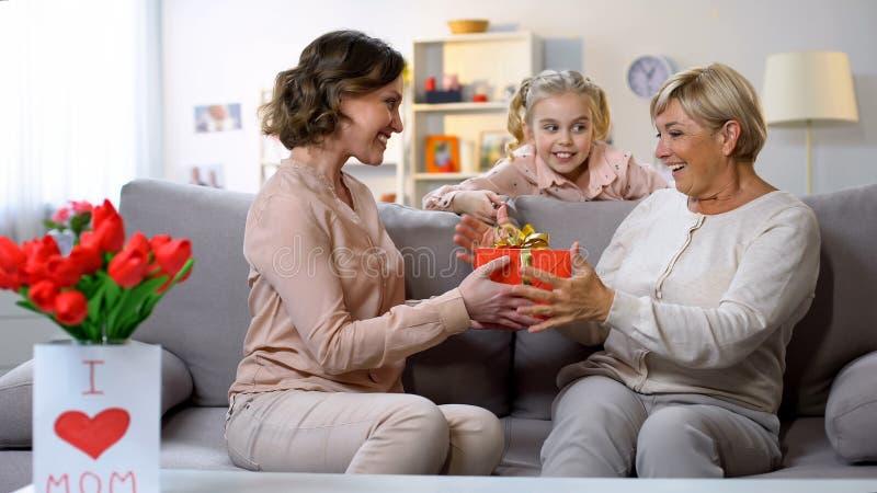 Vrouw die doos van de oma de rode gift, meisje voorstellen die haar gelukwensen met moedersdag stock afbeelding