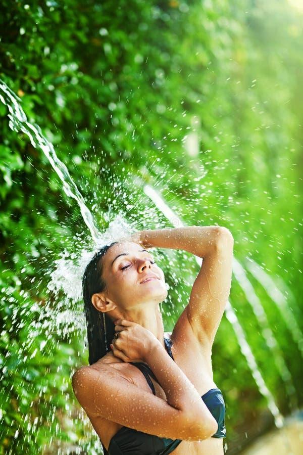 Vrouw die douche hebben onder tropische waterval royalty-vrije stock foto