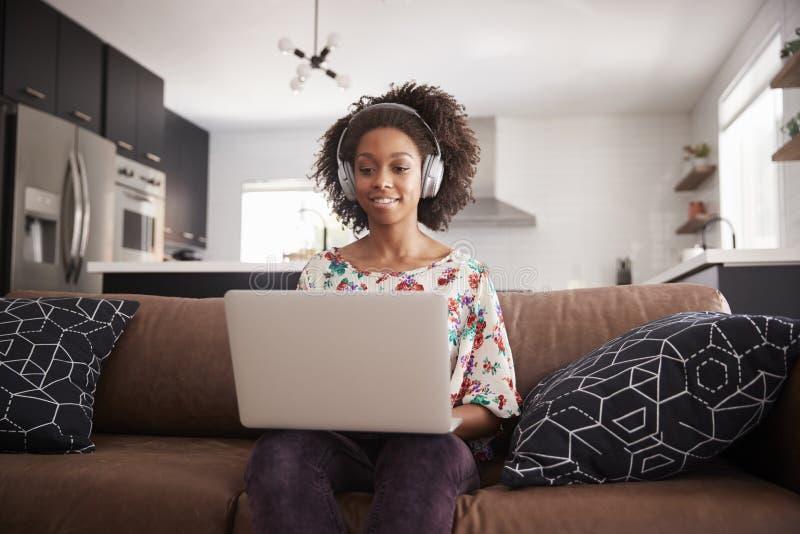 Vrouw die Draadloze Hoofdtelefoons dragen die op Sofa At Home Using Laptop zitten royalty-vrije stock foto