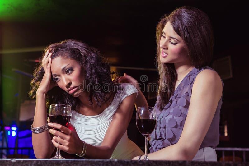 Vrouw die dranken hebben en haar gedeprimeerde vriend troosten royalty-vrije stock foto's