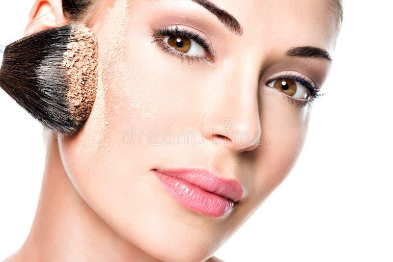 Vrouw die droge kosmetische toon- stichting op het gezicht toepassen stock foto's