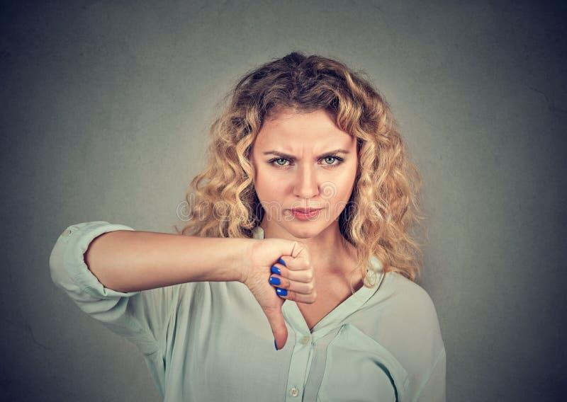 Vrouw die duim onderaan gebaar geven die met negatieve uitdrukking kijken royalty-vrije stock foto