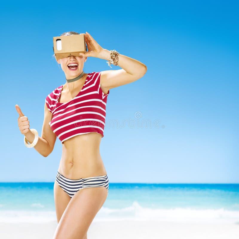 Vrouw die duimen tonen en virtueel werkelijkheidstoestel dragen royalty-vrije stock afbeeldingen