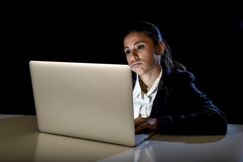 Vrouw die in duisternis aan laptop computer laat bij nacht werken die beklemtoond en vermoeid bored kijken royalty-vrije stock foto's