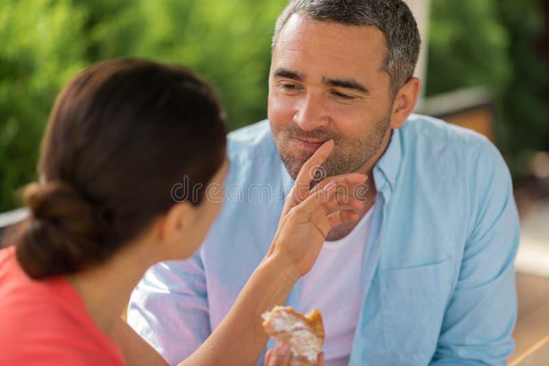 Vrouw die echtgenoot behandelen terwijl het voeden van hem met croissant royalty-vrije stock foto