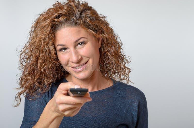 Vrouw die een afstandsbediening houdt royalty-vrije stock fotografie