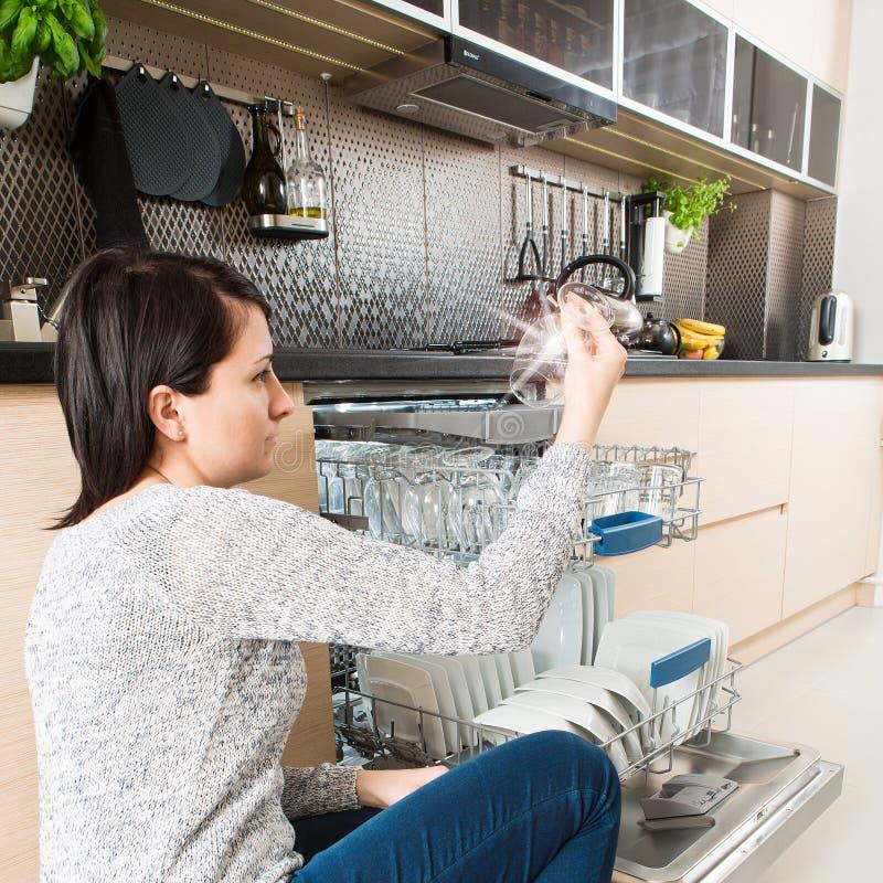Vrouw die een afwasmachine in een moderne keuken met behulp van royalty-vrije stock fotografie