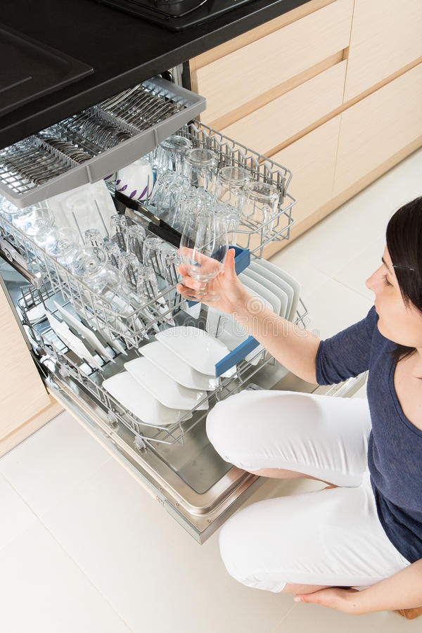 Vrouw die een afwasmachine in een moderne keuken met behulp van royalty-vrije stock afbeelding