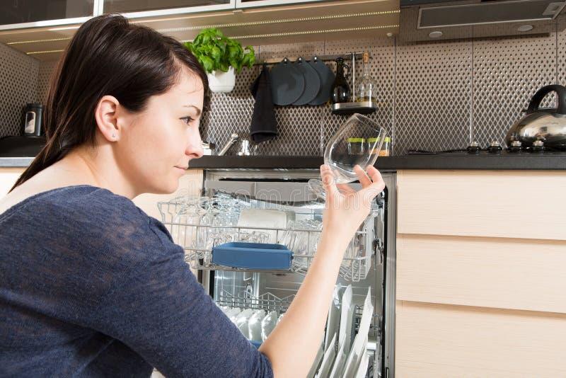 Vrouw die een afwasmachine in een moderne keuken met behulp van royalty-vrije stock foto's