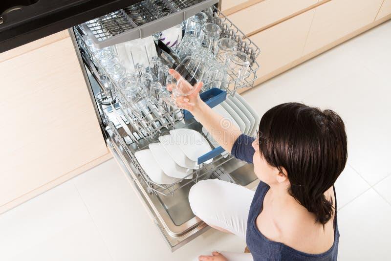 Vrouw die een afwasmachine in een moderne keuken met behulp van stock afbeeldingen