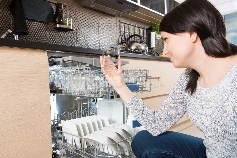 Vrouw die een afwasmachine in een moderne keuken met behulp van stock foto's