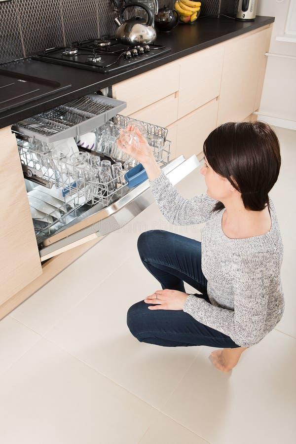 Vrouw die een afwasmachine in een moderne keuken met behulp van stock afbeelding