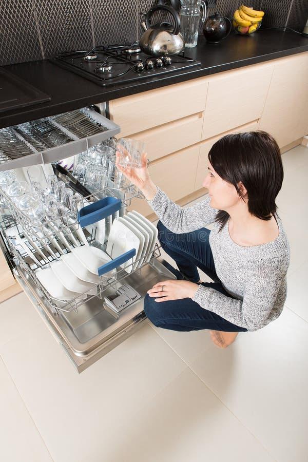 Vrouw die een afwasmachine in een moderne keuken met behulp van stock fotografie