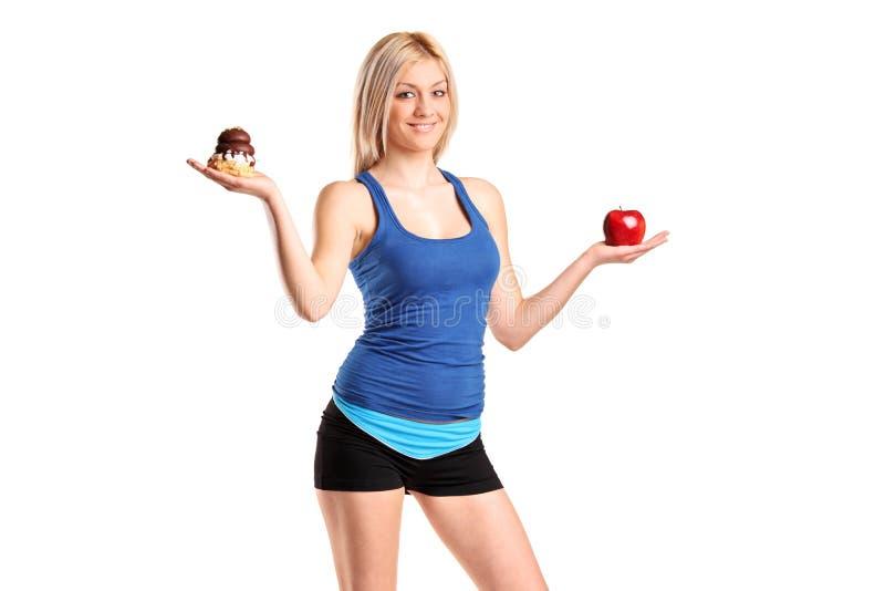 Vrouw die een appel en een plak van cake houdt royalty-vrije stock fotografie