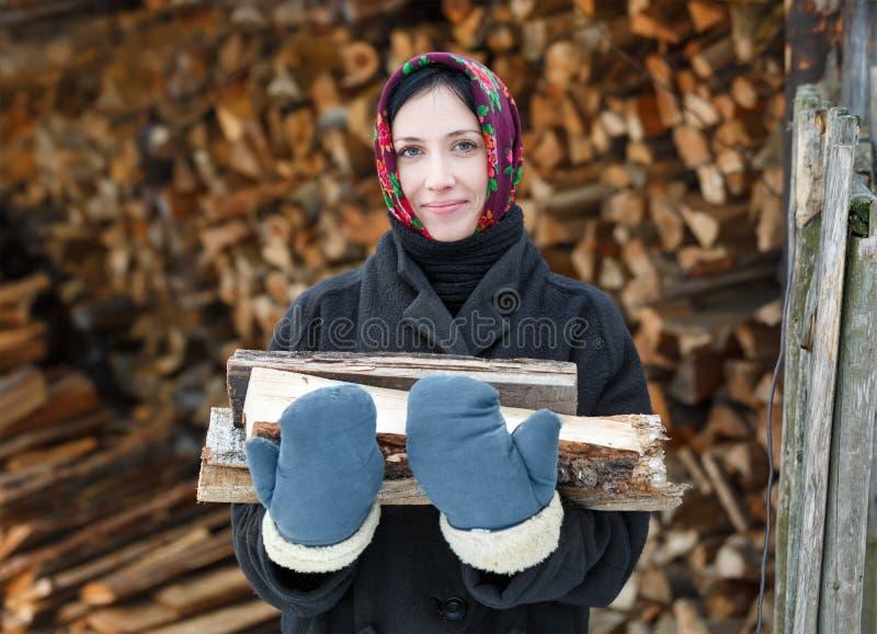 Vrouw die een armvol hout houden stock afbeeldingen