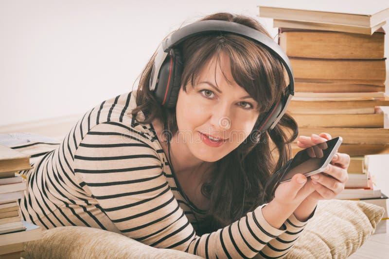 Vrouw die een audiobook luisteren stock fotografie