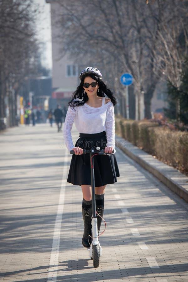Vrouw die een autoped berijdt Donkerbruine duwen van de weg royalty-vrije stock afbeeldingen