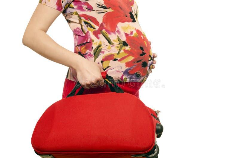 Vrouw die een baby verwachten die een koffer in haar handen houden stock foto's