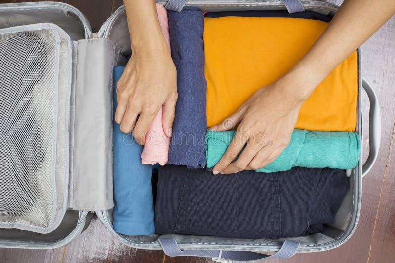 Vrouw die een bagage voor een nieuwe reis inpakken stock afbeelding