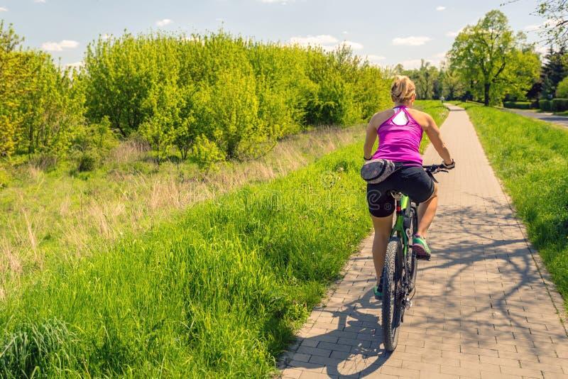 Vrouw die een bergfiets in stadspark cirkelen, de zomerdag stock foto