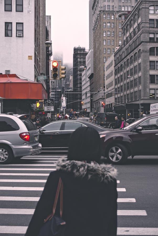 Vrouw die een bezige weg wachten te kruisen stock afbeeldingen