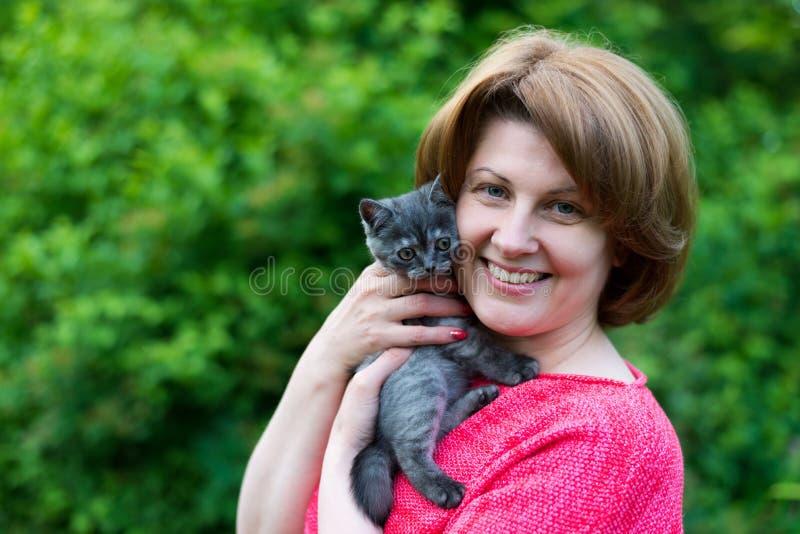 Vrouw die een blauwe katjes Schotse Straat in openlucht koesteren in stock afbeelding