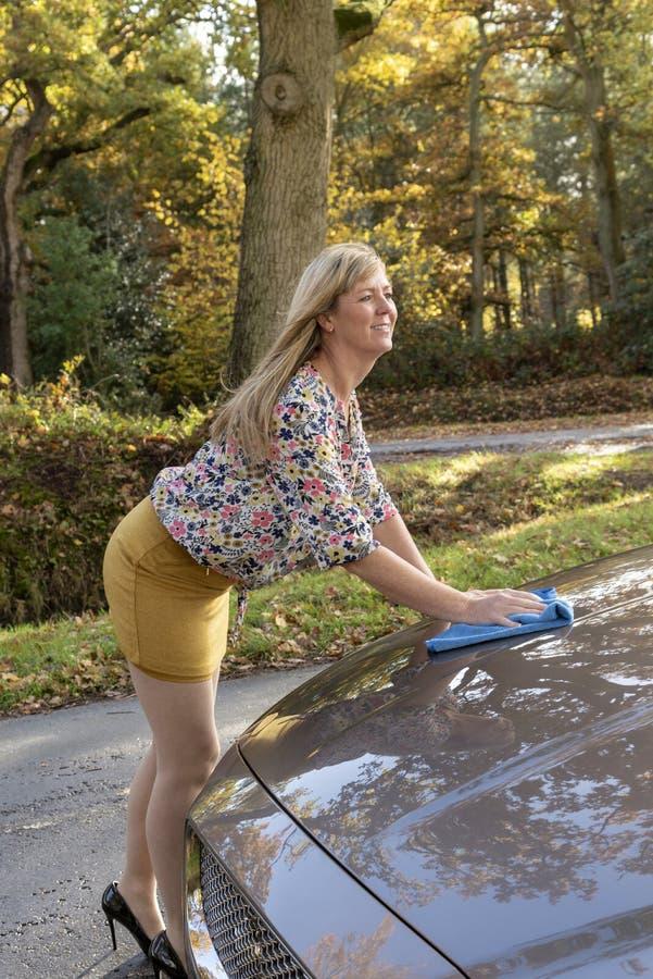 Vrouw die een bloemenoverhemd dragen die haar auto oppoetsen stock afbeelding