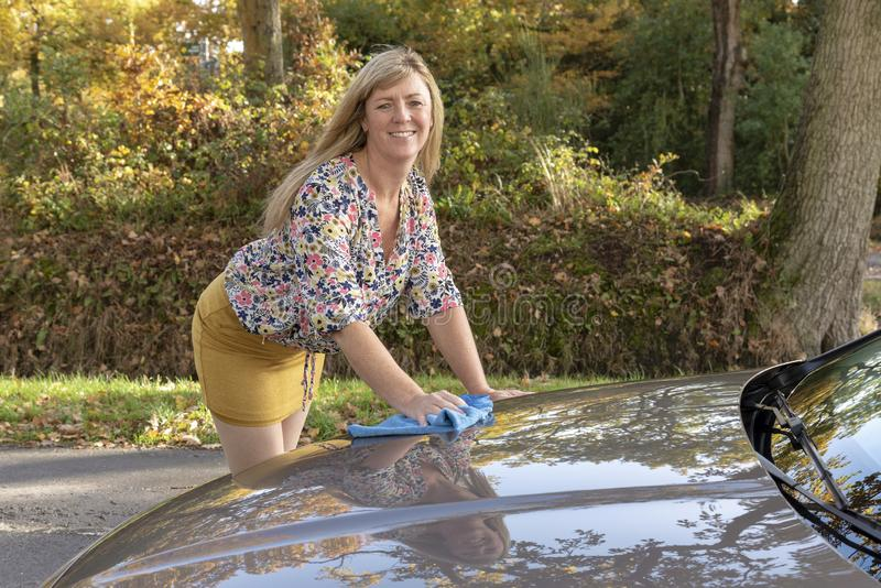 Vrouw die een bloemenoverhemd dragen die haar auto oppoetsen royalty-vrije stock afbeeldingen