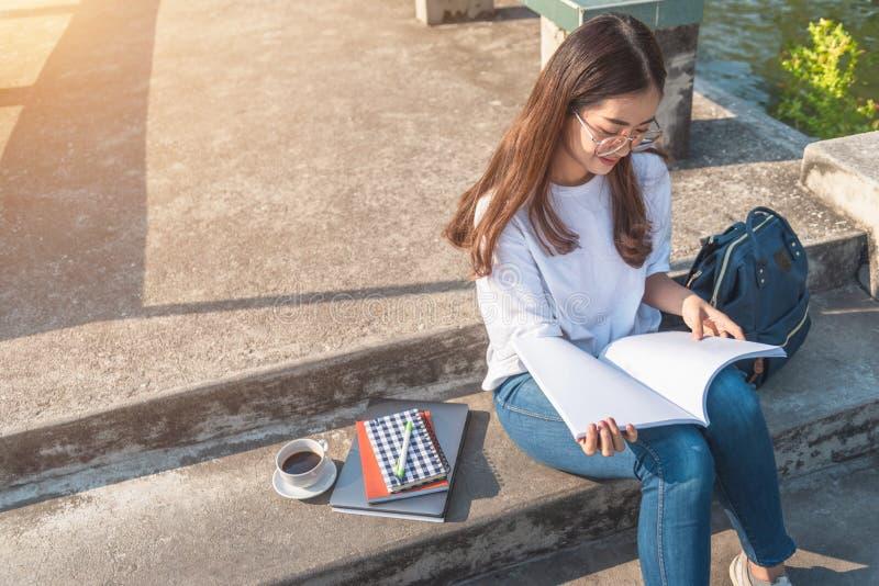 Vrouw die een boek in het park leest stock afbeeldingen