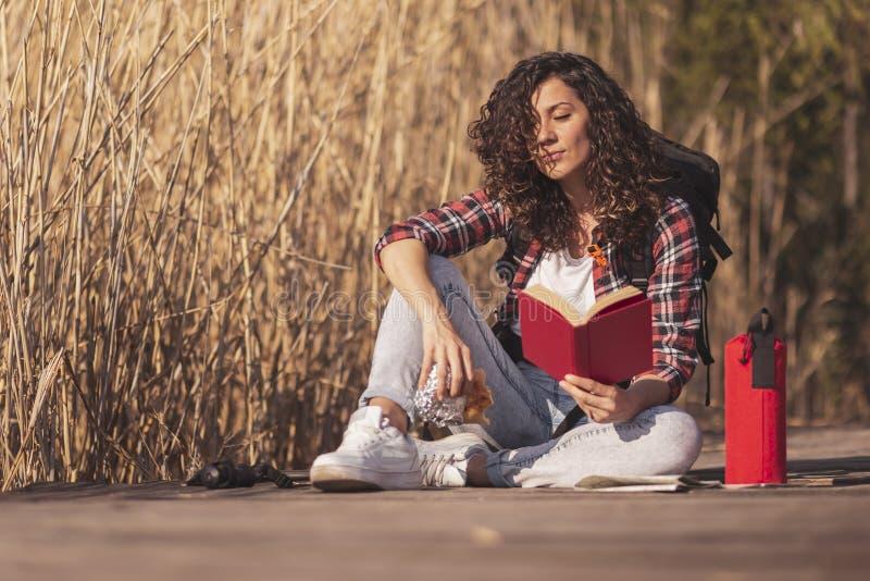 Vrouw die een boek lezen door het meer stock fotografie