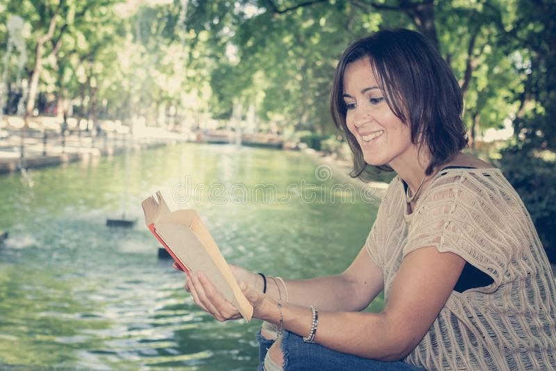 Vrouw die een boek in een park leest royalty-vrije stock afbeelding