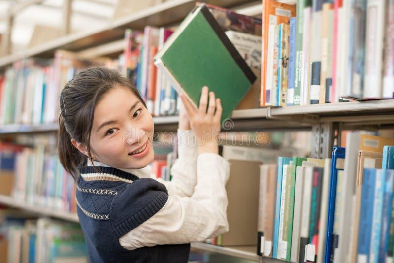 Vrouw die een boek van een boekenrek nemen royalty-vrije stock afbeeldingen