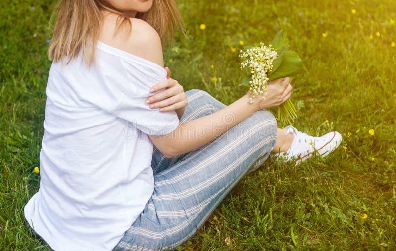 Vrouw die een boeket van lilly van valleibloemen houden stock foto
