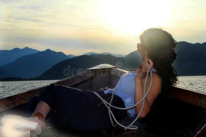 Vrouw die in een boot liggen en de afstand onderzoeken stock afbeelding