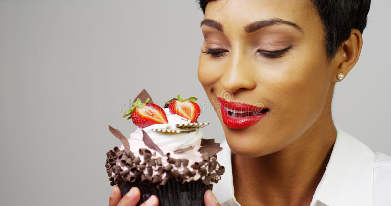 Vrouw die een buitensporig dessert bewonderen cupcake stock fotografie